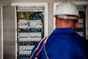Elektryk w pracy - z kaskiem na głowie i kablami - myśli o pieniądzach