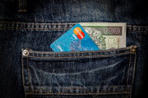 karta płatnicza i 100 złotych w kieszeniach